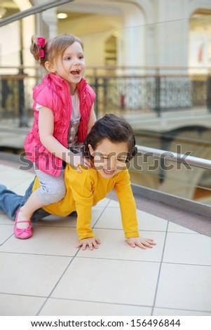 Little cute girl and boy play on floor in big mall. Girl saddled boy.
