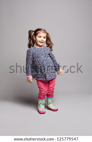 little cute girl dancing and enjoying on grey background