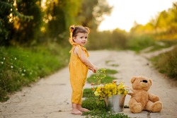 Little Cute Girl dressed in yellow clothes in the park, played with a teddy bear.