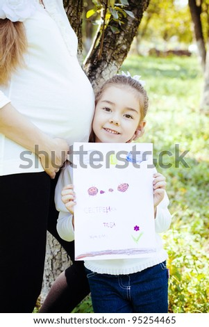 stock photo little cute girl drew a picture for pregnant mothers as a gift a girl standing next to her mother 95254465 Gabby — pregnant wet hair nude with sunglasses at the beach leaning on left ...