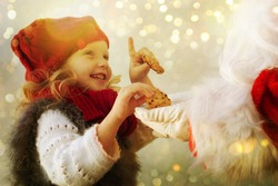 Little cute girl giving cookies to Santa Claus