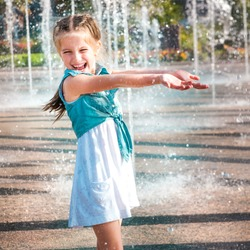 little cute girl having fun in splashes a fountain