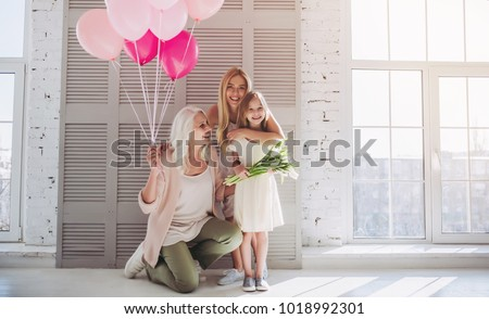 Little cute girl, her attractive young mother and charming grandmother are standing with air balloons and flowers in light room. Women's generation. International Women's Day. Happy Mother's Day. #1018992301
