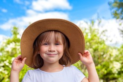 Little cute girl in a big hat on the background of trees and sky.