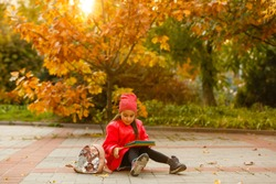 Little cute girl in autumn park. Schoolgirl with a backpack.The concept of autumn, school, study, education, childhood, back to school.