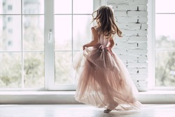 Little cute girl in beautiful dress is dancing near the window at home.
