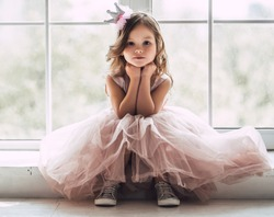 Little cute girl in beautiful dress is sitting near the window at home.