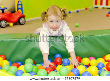 Little cute girl in playroom with colourful balls