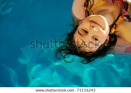 Little cute girl in pool with copy space