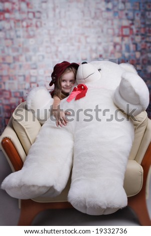Little cute girl in red dress with big smile holding huge Teddy bear.
