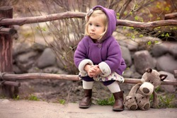 little cute girl in the purple coat with hood is sitting near the wooden fence with her toy wolf