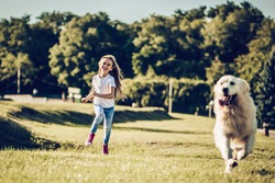 Little cute girl is having fun with golden retriever on a green grass. Charming cheerful girl is running with dog labrador in park.