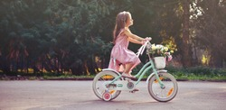Little cute girl is riding a bicycle with flowers in the park. Vintage kid's portrait.