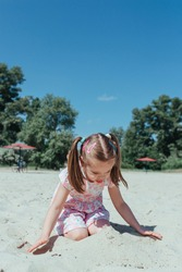 Little cute girl on beach. little girl playing in the sand.
