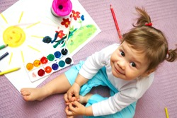 Little cute girl painting sun inside
