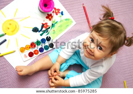 Little cute girl painting sun inside