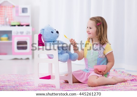 Little cute girl playing with her teddy bear. Child feeding doll in white nursery. Children play with wooden educational toys. Toddler kid in a playroom. Kids feed dolls and cook in toy kitchen.