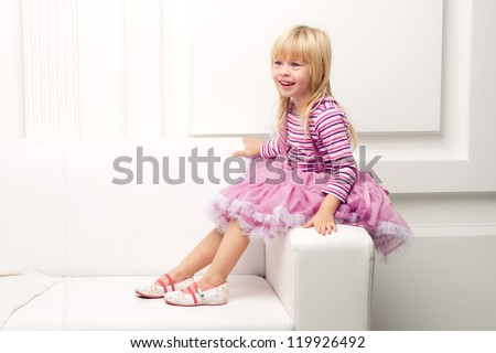Little cute girl posing happily on sofa