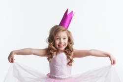 Little cute girl posing in pink halloween princess costume and crown isolated on white background