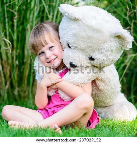 Little cute girl sitting in the grass with large teddy bear on her back