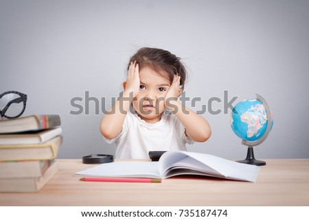 little cute girl suffering from headache while doing overwork with learning , homework , study and exam. school children education habit and parent concern concept.