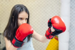 little cute girl trains in the boxing gloves, blurred background