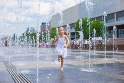 Little cute girl walking in open street fountain at hot sunny day