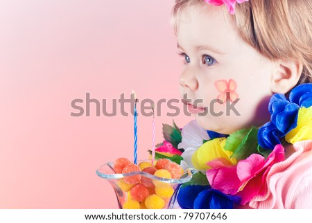 little cute girl wearing a Hawaiian Rainbow Lei  waiting to blow out the two candles in her birthday cake isolated over  background