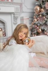 Little cute girl with blond hair with angel wings in the studio next to the Christmas tree and with Christmas balls