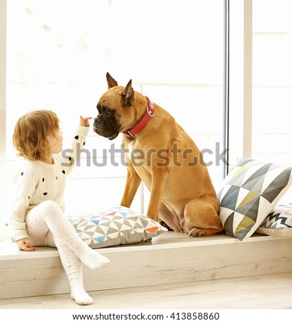 Little cute girl with boxer dog sitting on windowsill at home