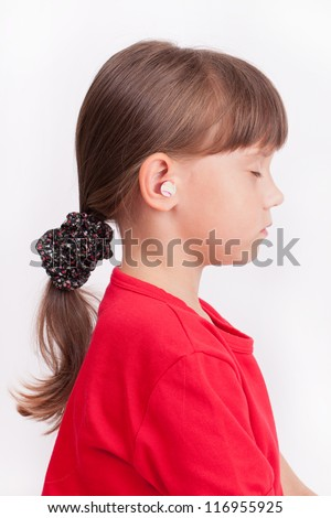Little cute girl with ear plugs in his ears