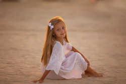 Little cute girl with long hair in a white tunic posing looking at the camera on the sand at sunset
