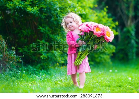 Little cute girl with peony flowers. Child wearing a pink dress playing in a summer garden. Kids gardening. Children play outdoors. Toddler kid with flower bouquet for birthday or mother\'s day.