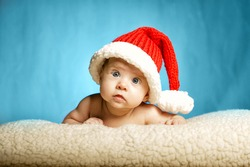 little cute girl with santa hat on blue background