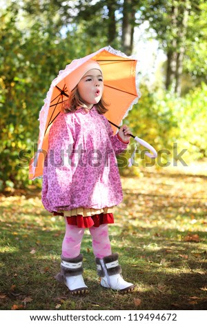little cute girl with umbrella in autumn park