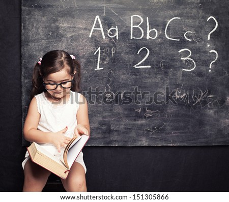 little cute girls looking for answers in front of blackboard