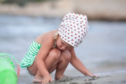 Little cute happy girl plays and swims in the sea, Spain
