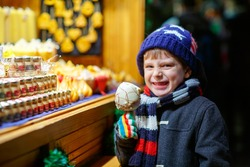 Little cute kid boy eating sugar apple near sweet stand with gingerbread and nuts. Happy child on Christmas market in Germany. Traditional leisure on xmas. Holiday, celebration, childhood.