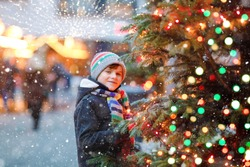 Little cute kid boy having fun on traditional Christmas market during strong snowfall. Happy child enjoying traditional family market in Germany. Schoolboy standing by illuminated xmas tree.