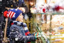 Little cute kid boy near sweet stand with gingerbread and nuts. Happy child on Christmas market in Germany. Traditional leisure for families on xmas. Holiday, celebration, tradition, childhood.
