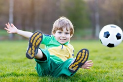 Little cute kid boy of 4 playing soccer with football on field, outdoors. Active child making sports with kids or father, Smiling happy preschool boy having fun in summer.