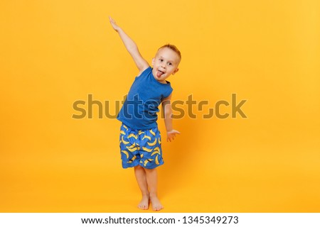 Little cute kid boy 3-4 years old wearing blue beach summer clothes isolated on bright yellow orange wall background, children studio portrait. People, childhood lifestyle concept. Mock up copy space #1345349273