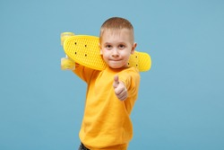 Little cute kid boy 4-5 years old wearing yellow clothes hold in hand skateboard isolated on pastel blue wall background, children studio portrait. People sincere emotions childhood lifestyle concept