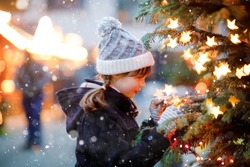 Little cute kid girl having fun on traditional Christmas market during strong snowfall. Happy child enjoying traditional family market in Germany. Schoolgirl standing by illuminated xmas tree.