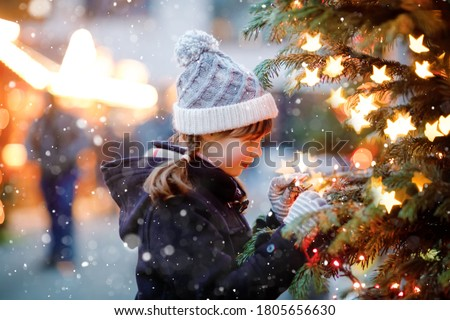 Photo of  Little cute kid girl having fun on traditional Christmas market during strong snowfall. Happy child enjoying traditional family market in Germany. Schoolgirl standing by illuminated xmas tree.