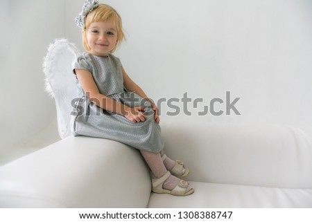 little cute little blonde girl in a gray dress with angelic white wings on a light sofa in the luminous room
