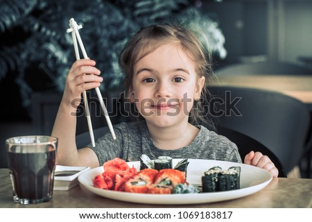 Little cute little girl eating sushi in a cafe, concept of eating