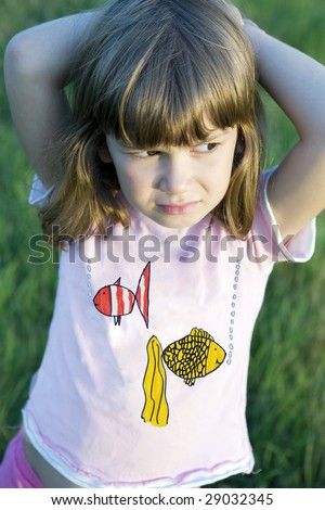 Little cute pensive  girl six years old standing in the middle of the meadow