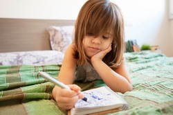 Little cute preschool girl lying on the bed in bedroom at home, she's bored and scribbling with blue pen on the paper notebook. Childhood concept. Leisure activity indoors. Getting bored at home.