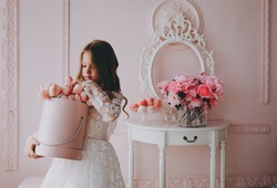 Little cute princess girl in white dress is holding flowers in a pink room.
